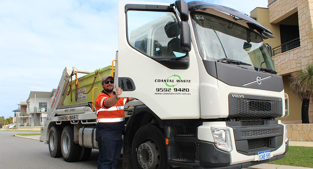 A coastal waste truck unloading a skip bin at a Perth house.